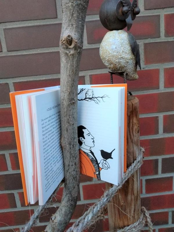 Buch an einem Buch darüber eine Eule aus Stein