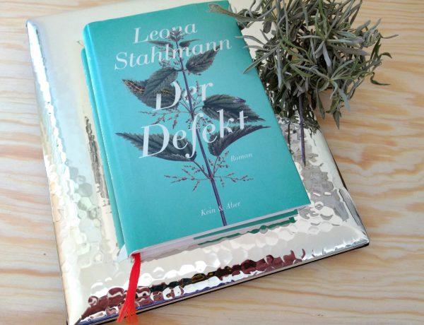 Türkisfarbenes Buch auf dem Cover eine Brennnessel auf einem silbernen Bilderrahmen