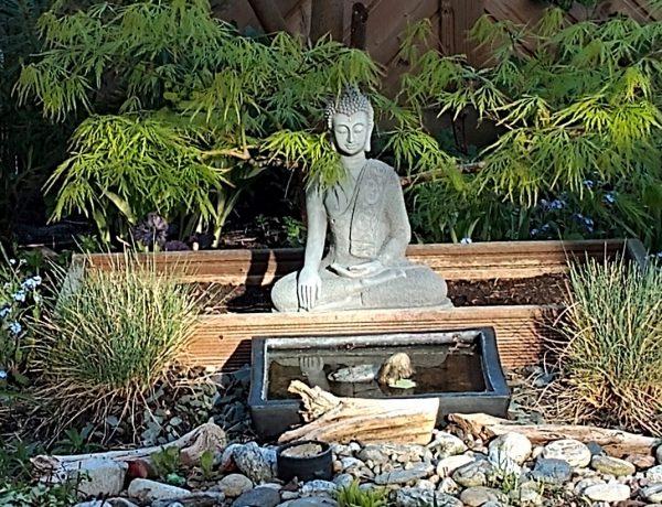 Buddha im Garten davor ein kleines Wasserbecken