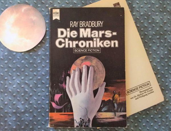 Roman auf einer Metallfläche, daneben ein Mars aus Papier