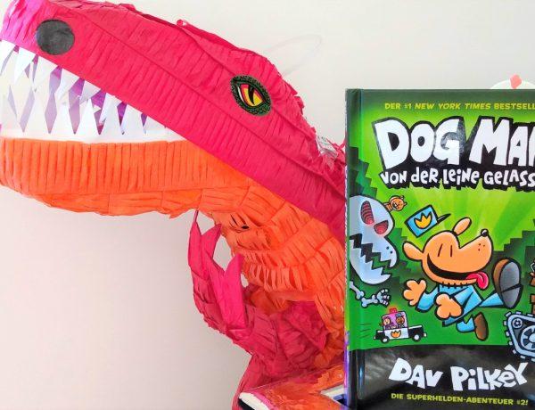 Dog Man Comic neben einem großen roten T-Rex aus Papier