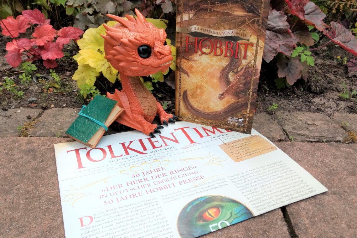 Funko Figur von Smaug sitzt auf einer Ausgabe der Zeitung Tolkien Times, daneben die illustrierte Fassung vom Hobbit mit einem feuerspeienden Drachen darauf - das alles vor Pflanzen