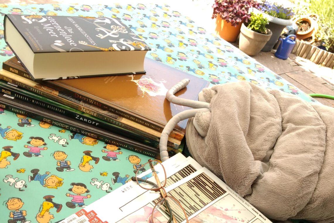 Plüschassel neben einem Stapel Comics und einem Buch, alles auf einer Peanuts-Tischdecke im Garten