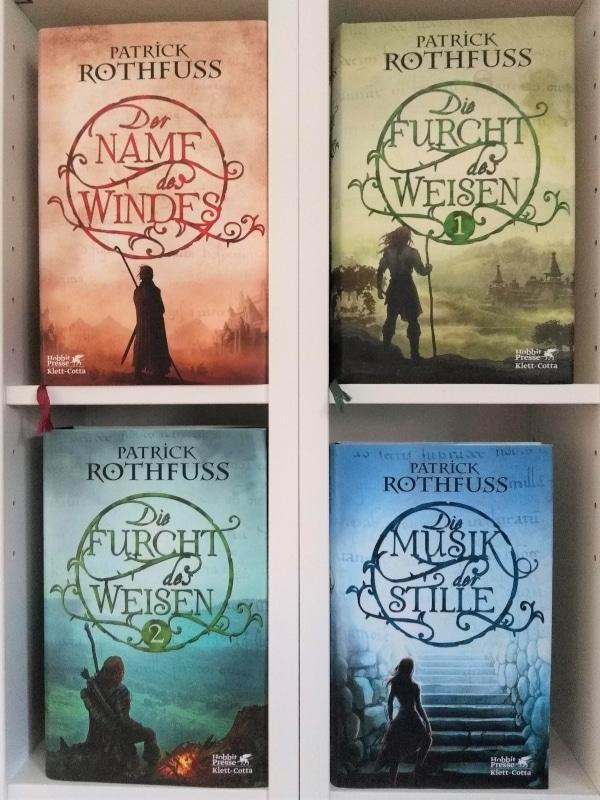 Alle Bücher von Patrick Rothfuss im Regal - in zwei Reihen mit dem Cover nach vorn.
