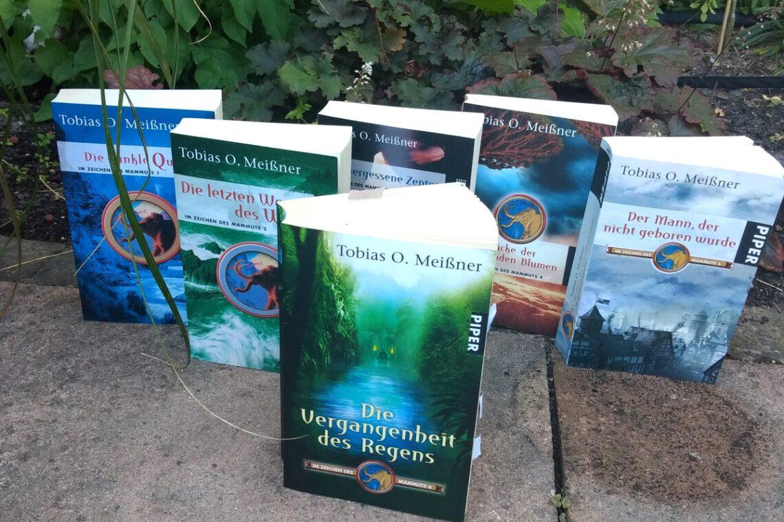 6 Bücher der Reihe aufrecht stehend vor Pflanzen und auf Steinplaten