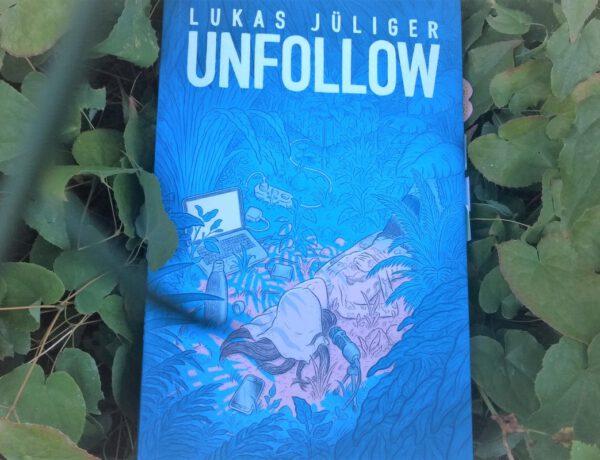 blau-türkiser Comic liegt in einem Bett aus grünen Pflanzen