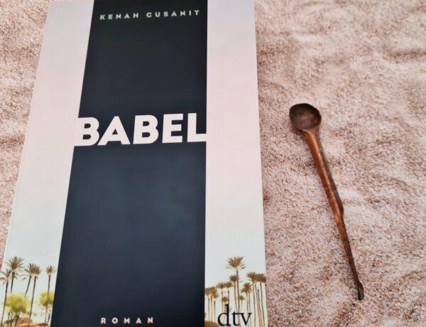 Buch mit einem vertikalen schwarzen breiten Streifen - Aufschrift BABEL liegt auf Sand