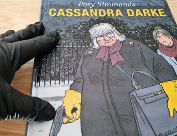Comic zeigt eine dicke ältere Frau mit Mütze, gelben Gummihandschuhen und einem Revolver, Comic wird von einer Hand in Gummihandschuh präsentiert