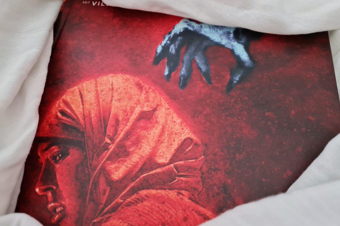 Cover zeigt Frau in rot, bedroh von einer grauen untoten Hand über ihr