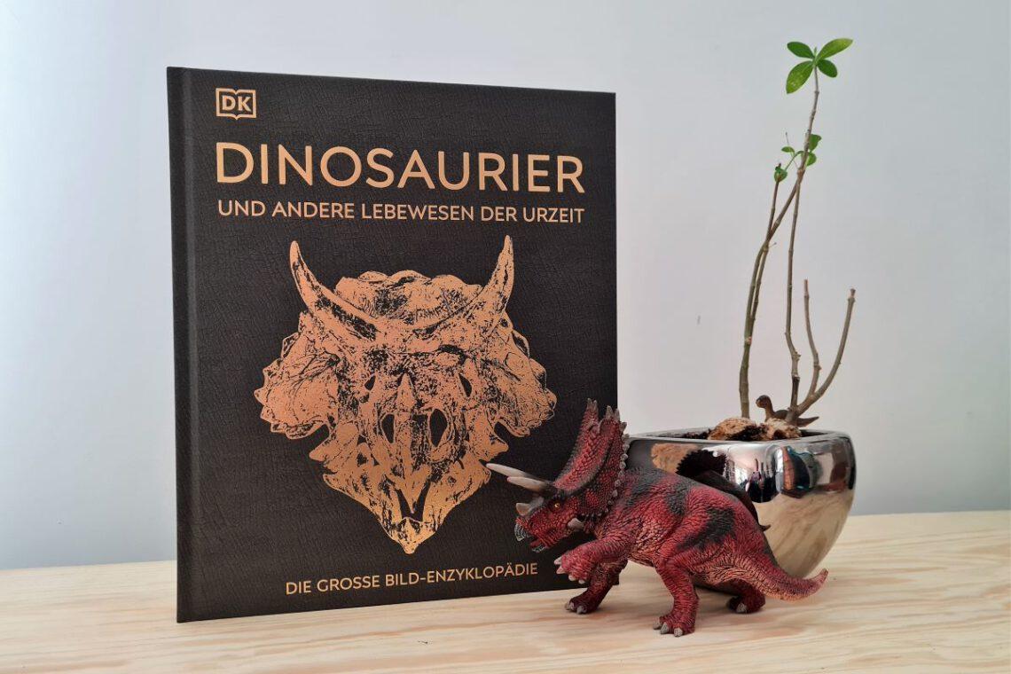 Buch Dinosaurier steht neben einer Dinosaurierfigur und daneben eine Pflanze in silbernem Topf