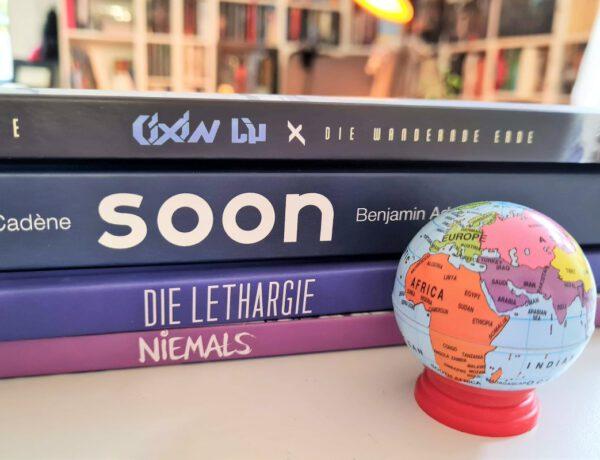 Vier Comics auf einem Stapel davor ein kleiner Globus im Hintergrund ein Bücherregal