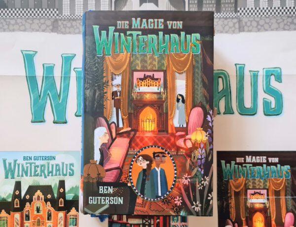Cover zeigt das Kaminzimmer des Hotels und dabei liegt das Buch auf einem Poster der Buchreihe