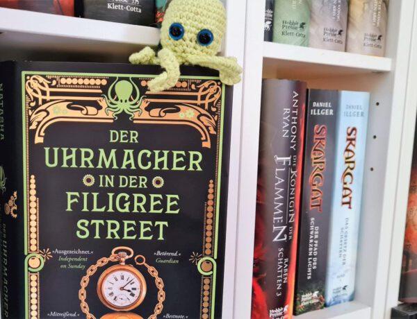 Buch steht frontal im Regal, obenauf sitzt ein kleiner grüner gehäkelter Oktopus